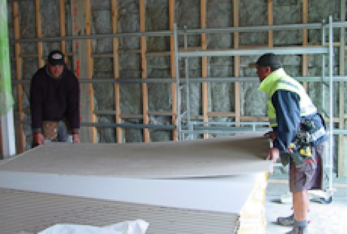 A building contractor and a labourer moving a sheet of plasterboard