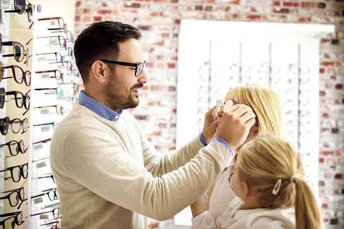 A dispensing optician fits a pair of glasses to a woman as a little girl watches