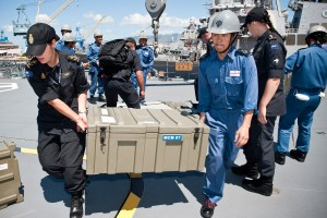 Two navy soldiers carry a big box of weapons off a navy frigate