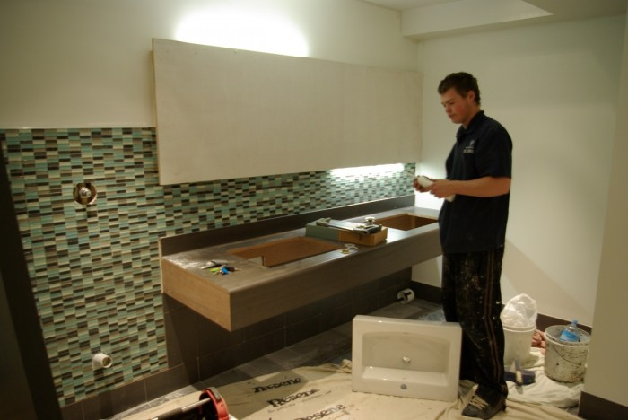 Andrew Dodge standing in a bathroom with a sink ready to install