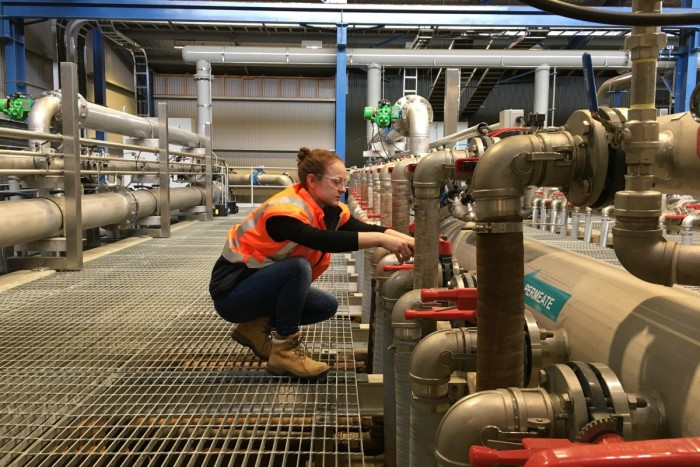 A water treatment operator checks pipes in a water treatment plant