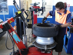 A tyre technician removes a tyre from a wheel rim.